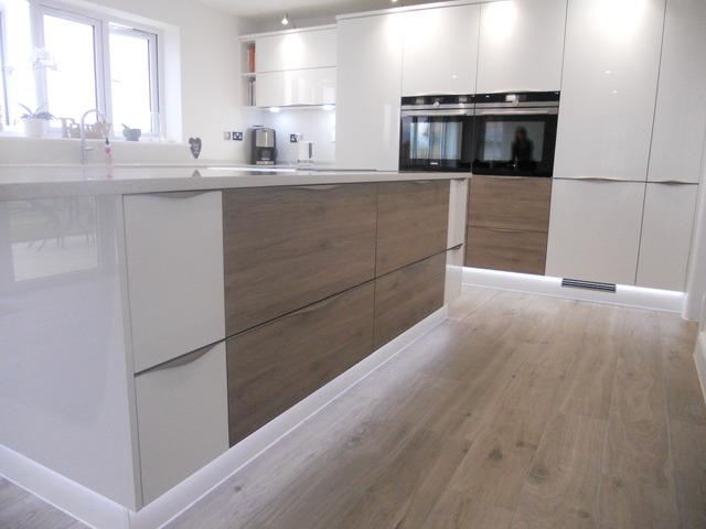 Stunning german kitchen with white gloss woodgrain doors for Wood grain kitchen doors